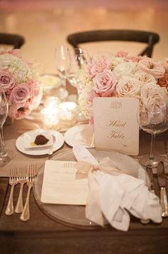Gorgeous place settings include dinner menus and napkins tied with soft pink ribbons.