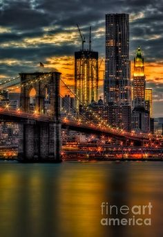 Sunset view to the Brooklyn Bridge with the Freedom Tower, Frank Gehry Skyscraper and the Woolworth Building. Susan Candelario New York City NYC