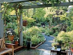 """For drama, owner Guillermo designed the pergolas near the garden's entrance as a wisteria-covered, shady tunnel to the open and bright larger area beyond.Guillermo has no regrets about chucking his deskbound banking career for the green world of garden design. """"Now I start my day by seeing what's new in the garden,"""" he says. """"It's very relaxing."""" (Photo: Richard Warren)"""