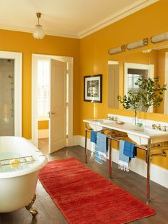 In the principal bathroom, the mustard yellow walls tie in the wallpaper from the master bedroom.