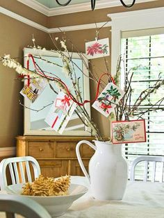 "Christmas cards adorn a centerpiece ""tree"" made with twigs from your yard. Arrange twigs in a pitcher or vase, and clip or tie cards to twig ends. For an added burst of holiday color, weave a red ribbon or piece of rickrack through the display."