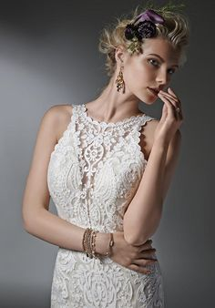 Timeless and elegant, this lace sheath wedding dress features a modern illusion deep V halter neckline, a stunning, scalloped plunging back, and illusion straps. Finished with covered buttons over zipper closure.
