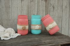 3 quart size mason jars hand painted in coral and aqua with a ribbon of burlap and lace, and a burlap flower, lightly distressed with a protective coating.