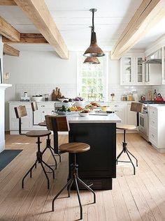 Love this industrial-meets-modern kitchen with rustic stools and pendant lights.