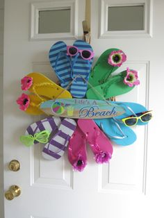 Flip flop wreath that I made - they're super easy to make! I got all of the supplies from the dollar store, too!! All you do is take a wreath base and hot glue flip flops to it in any design that you would like. Then decorate with flowers, gemstones, sunglasses, beach stuff, signs, etc. I used a paper twist that I unraveled and slipped it around the wreath and tied into a bow to hang on my door. So easy!