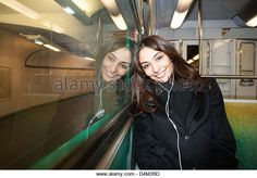Woman listening to earphones on subway - Stock Image