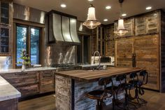This imaginative kitchen combines unique elements to create a rustic vintage aesthetic. The diverse materials include reclaimed pine cabinetry, chicken wire, antique telephone-operator barstools and a mix of white marble and walnut countertops.