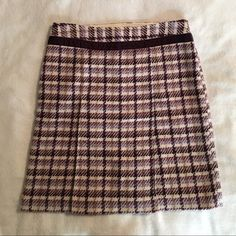 Ann Taylor Pleat Front Skirt Beautiful purple/off white plaid wool skirt!! Size 4. Zips on the side. 20 in long. Waist 14 in. Skirt is lined. Shell: 53% wool 20% polyester 16% nylon 10% acrylic. Purple velvet strip around waist. Excellent condition!!! Ann Taylor Skirts
