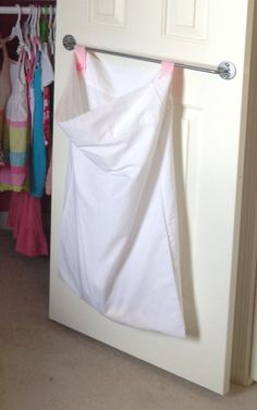 Pillow case turned laundry hamper. The addition of ribbon and buttons make it ready to hang from Ikea BYGEL rail mounted to inside of closet door.