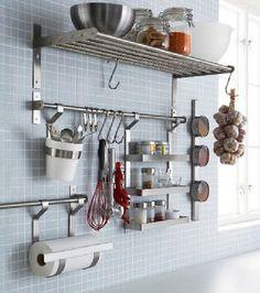Une bonne astuce pour regrouper les accessoires de cuisine sur un seul mur, des barres inox équipées de crochets posées sous une étagère grill Ikea. Pots d'épices, batterie d'ustensiles sont accessibles facilement.