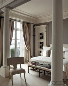A pair of Tus­can columns and an 18th-century Swedish klismos chair in a bedroom. - ELLEDecor.com