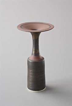Lucie Rie, Vase with flaring lip, Porcelain, bright gold manganese and dry terra-cotta glazes. Painted black bands on the shoulder and lip. 23 cm. (9 in.) high, 1985