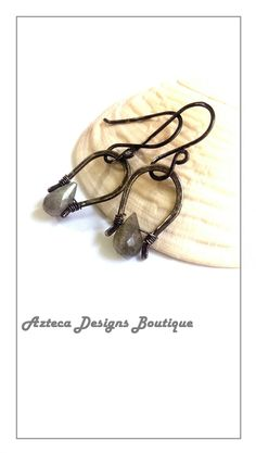 Stunning, shimmery genuine Labradorite briolettes are wire wrapped onto hand forged, hammered and oxidized solid sterling silver frames!! These darling beauties hang from hand forged, hammered, and oxidized sterling silver ear wires! This simple design enhances the natural beauty of the gem, and allows it to shine! These earrings are so versatile, and perfect for an evening out, or look great with casual dress!Length: 1 and 1/2 inches.Enjoy complimentary gift packaging!
