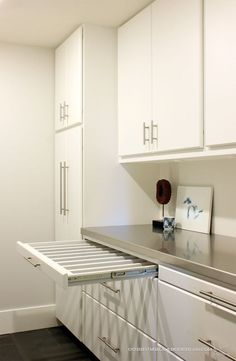 Pull-out drying racks for the laundry room | modern utility rooms with stainless steel counters for worktop