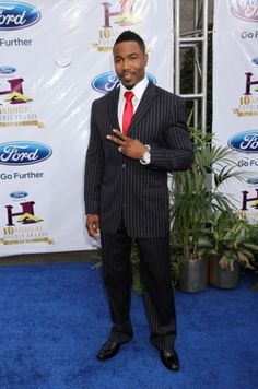 Michael Jai White wears a pinstriped black and white suit