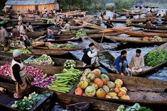 Photo by @stevemccurryofficial // Scores of shikaras filled with fruits and vegetables jostle for space on Dal Lake Kashmir as farmers transact the early morning business of Srinagar's wholesale produce market. Some farmers tend floating gardens: They weave stalks of water plants into a living offshore raft cover it with soil and then plant crops. by natgeo
