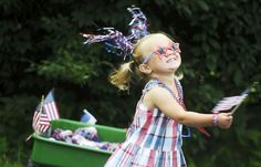 Grace Brown, 2, of Springfield Township waves her flags before the children's parade, part of the Fourth of July Blast in Jacobus last year.