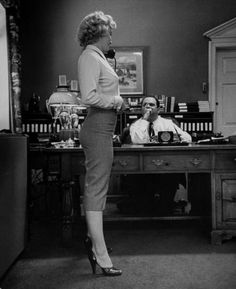 """Marilyn Monroe talking on the phone during an interview for the movie """"Clash by Night,"""" while producer Jerry Wald looks on, 1951."""