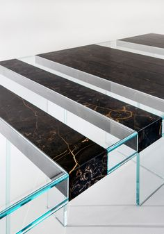 Elemento Table by Paolo Nicolò Rusolen. It is a modular table which can grow in lenght by adding elements. The origins of the project lie in the idea of building an extremely light-looking table, based on the alternation of composite materials, thus creating an 'empty-full' effect. The table top, with its sequence of glass and stone supported by two fully transparent bases, almost appears to be floating in space.   Laurameroni