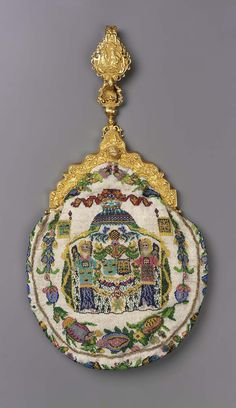 Chatelaine bag. France, 1870-85. Strung glass beads (sablé) held together with looping stitches. Polychrome design on white ground: two coats of arms flanked by 2 angels holding standards under canopy, vegetative border (obv.); woman in early 18th century costume seated at dressing table (rev.). Large hinged gold frame with classical motifs, stud closure, chain with hook (6 marks in frame, 3 in hook). Two interior compartments lined in salmon silk.