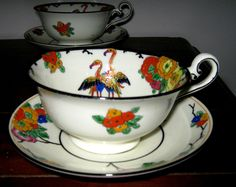 Doulton deco: unnamed cup duos by Robert Allen, H2958, RA248a, Rd 727519, c1926 (pattern). Flamingos, branched flowers and foliage in vibrant reds, oranges and blues with yellow banded border and black shadowing effects, highlights and trim.