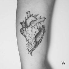 Surrealist anatomical heart sea snail tattoo on the left inner arm.