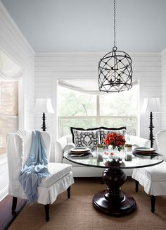 Heather Scott Home - dining rooms - Benjamin Moore - Ice Cap - Chenonceau Fabric, pillows, white, slipcover, settee, baby blue, painted, ceiling, iron, cage, chandelier, glass-top, pedestal, table, sisal, rug, black, border, black, floor lamps, white, slipcover, wingback, chairs, wingback chairs, white wingback chairs, slipcovered wingback chairs,