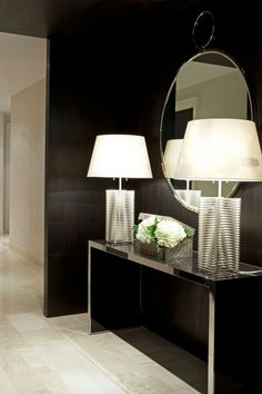 Black is always a good and classic option. In this entryway we can see a glamorous and luxurious ambiance created by black color pattern and reflected by this mirrored console.