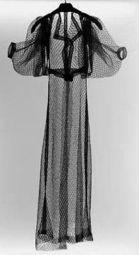 Schiaparelli uses new material at the time creating transparent and translucent outfits such as this tulle trench coat