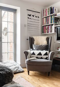 The family room at the rear of the house leads out into the back garden through these French windows, which allow the natural light to stream through. More books are stored on the Scandinavian String shelving system.
