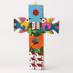"""Gifts of Faith - La Palma Dove Cross Brightly colored cross with inscription, """"God is Love."""" White pine is hand painted in the La Palma folk art style. Proceeds from your fair trade purchase support the economic recovery of rural artisans impacted by El Salvador's civil conflict. 10in.L x 7 1/4in.W x 1/2in.d $25"""