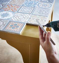 Die Tischplatte eines goldfarbenen IKEA LACK Beistelltisches wird mit Dekofliesen verziert.