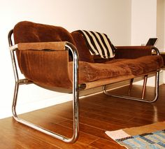 Mid century set features chrome tubular frame with a brown corduroy sling fabric seat and corduroy fabric pillows that are suspended. The labels are missing but they seem to be inspired by Marcel...