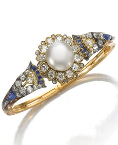 An antique natural pearl, sapphire and diamond bangle, Mellerio dits Meller, circa 1880. Of floral design, the centre set with a button-shaped natural pearl, highlighted with pear-shaped and calibré-cut sapphires, circular-, single-cut and rose diamonds, hinged. #MellerioDitsMeller #antique #bangle