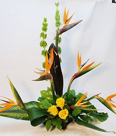 This fantastic contemporary arrangement of Birds of Paradise and exotic greenery can be the magic ticket to tropical places.