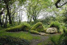 Escultura yacente . Dicha escultura se encuentra en el Jardín Perdido en Heligan (Estados unidos) . Tamaño : grande .Material :algun tipo de piedra junto con césped y arbustos . Textura :granulada . Acabado :Natural . Color : el color de la piedra , junto con diferentes gamas de verdes . Signficado : el contacto con la naturaleza nos hace sentir bien , aun que hoy dia no nos relacionamos con la naturaleza como lo hacian nuestros antepasados  , nos sigue aportando paz .