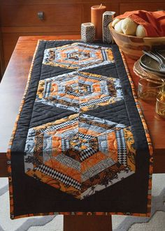 Everyone needs a Halloween table quilt pattern to work on, and this table runner is easy to make. Strip pieced triangles with festive prints are highlighted by a black background.