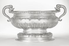 The Stowe Cistern. A massive George I silver two-handled wine cistern, Jacob Margas, London, 1714 bombé oval with gadroon & leaf-tip rim, neck engraved with the Buckingham arms, body with applied lobes & leaves between shoulder & foot applied with strapwork, shells & husks, scaled dolphin handles with open mouths, the interior fitted (probably later) with drain hole and later plug; fully marked on base, height 18 1/4 in.; length over handles 33 3/4 in. [Sold for  1,142,500 USD]