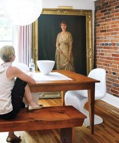 old portrait in modern interior; brick wall; farmhouse table