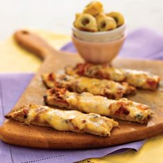 Pizza Sticks | Jarred bruschetta topping, chock full of flavorful herbs and veggies, saves both money and prep time for these cheesy pizza sticks.  Simply top a refrigerated thin pizza crust with the bruschetta topping and a shredded cheese blend, bake, and cut into bite-size strips.