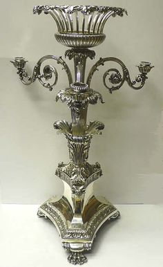 sterling silver center piece by the one of the great royal silversmiths of the early 19th century. The tall central column has 4 candelabra arms and is topped by an open work fruit bowl with trailing vine ornament.