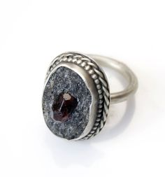 "Filigree sterling silver ring with garnet in schist stone. Oval stone measures .75"" at longest part. Due to the orgainc nature of the stone please allow for slight variation in color, size and placement of the garnet. MEMBER - Filomena's House"