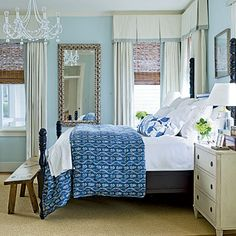 Soothing Blue Bedroom: Inspired by the harbor, the homeowners chose a calming blue palette and added an oyster shell-encrusted mirror. They mixed in elements that really bring the room to life—throw pillows and a killer light fixture.
