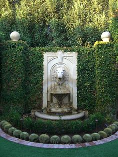 Old World style lion head fountain, surrounded by hedges and cactus. (image source unknown)