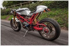 Ducati Monster SR2 Cafe Racer Ducati Cafe Racer based on Ducati Monster SR2 built by mechanical engineer John Grainge. Custom Cafe racer seat by Radical Ducati,  sub-frame was rebuilt, Custom fuel tank mounting and rear set was machined by john. Fuel tank was borroed from Ducati 749 and customized, Ohlins front suspension and disc brakes from Ducati 848, Ohlins rear suspension from Ducati 999, Ducati Hypermotard 1100S Marchesini magnesium wheels, Harley-Davidson V-Rod headlamp, Custom…