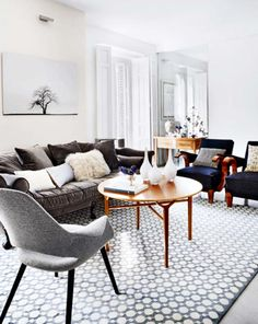 Living Room In An Apartment With A Geometric Print Rug, Dark Blue Grey  Velvet Sofa, Two Blue Armchairs, A Grey Upholstered Chair, And A Round Wood  Coffee ...