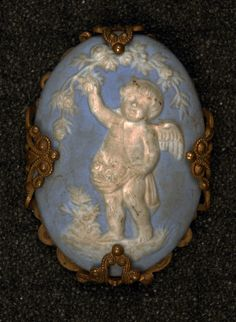 WEDGWOOD JASPERWARE BUTTON. Oval ceramic having white cherub picking apples on blue ground, set on a brass filigree diamond, the corners wrapped around the oval, loop shank mounted on bar at back.