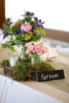Cluster centerpiece for the reception including mason jars, and mixed summer flowers.
