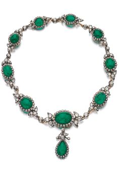 An antique emerald and diamond necklace, late 19th century. Set with cabochon emeralds framed with circular-cut diamonds, alternating with links of floral design set with cushion-shaped and rose diamonds, supporting a detachable pendant similarly set, length approximately 415mm. #antique #necklace