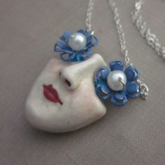 Two vintage blue enamelled metal flowers provide the eyes or sunglasses for this unusual porcelain clay pendant. The center of the flowers are wired in sterling silver wire with a white freshwater pearl in the center.